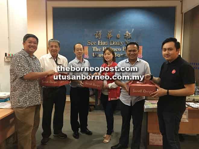 Francis (dua kiri), Saibi (dua kanan) dan Ling (tiga kiri) menerima kek daripada rombongan AirAsia yang diketuai Hamdan (kiri) di Kuching, semalam. Turut kelihatan, Mohammed Firdaus (kanan) dan Grace (tiga kanan).
