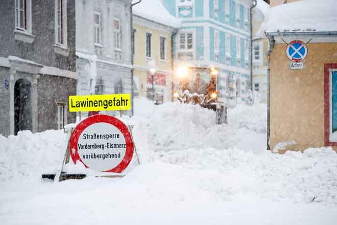 Sebuah tanda jalan yang menyebut 'bahaya salji runtuh' terpacak di sebuah lebuh yang diliputi salji di Vordernberg, Austria pada Khamis. — Gambar AFP