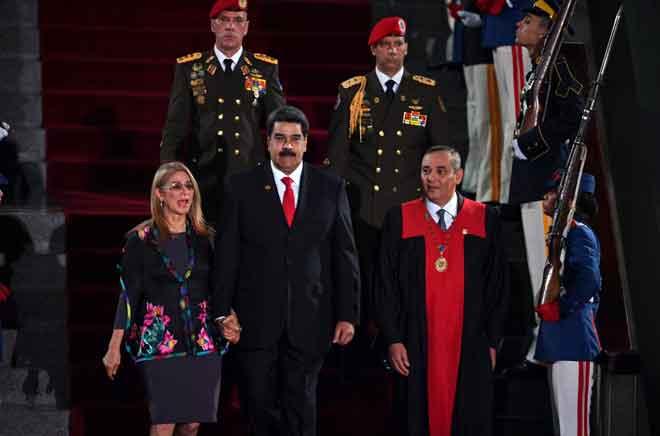 Maduro (tengah) berjalan bersama Wanita Pertama Cilia Flores dan presiden Mahkamah Keadilan Agung (TSJ) Maikel Moreno (kanan) selepas mereka tiba untuk majlis mengangkat sumpah bagi penggal keduanya, di Ibu Pejabat TSJ di Caracas, Venezuela pada Khamis. — Gambar AFP