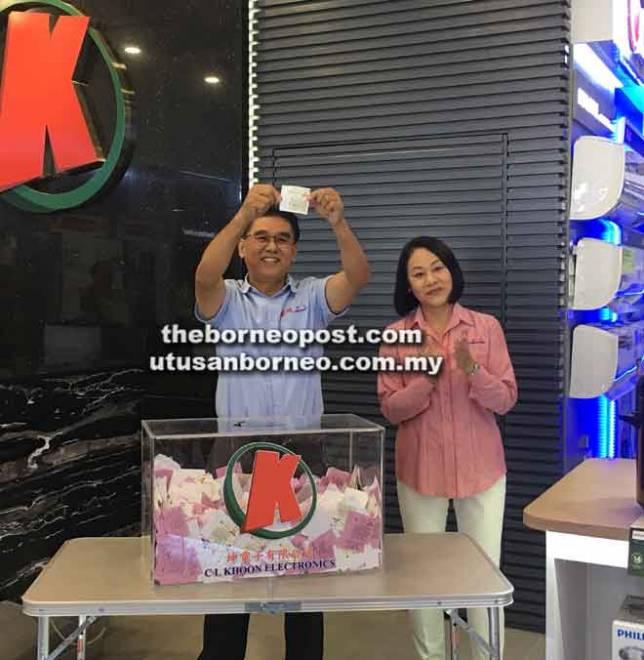 Lian Khoon (kiri) menunjukkan nama pemenang yang memenangi hadiah utama cabutan bertuah C L Khoon sempena ulang tahunnya yang ke-33 di cawangannya di Saradise Kuching, semalam. Turut kelihatan, Cybell Chin.