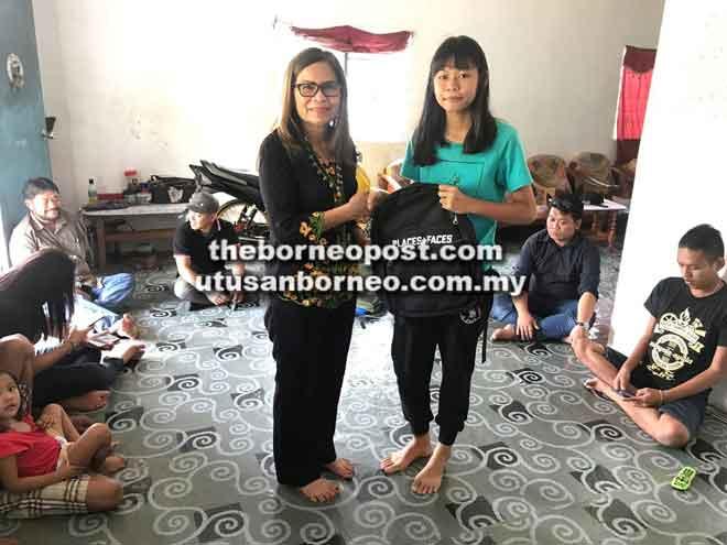 Norina menyerahkan beg sekolah serta peralatan persekolahan kepada Elviana.