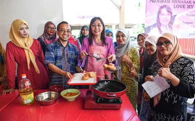 Teresa Kok (tengah) menunjukkan kuih donut yang telah di goreng menggunakan minyat sawit pada program memasak dan forum kesihatan 'Love My Palm Oil' ketika mengadakan lawatan ke Felda Sungai Koyan, semalam. — Gambar Bernama