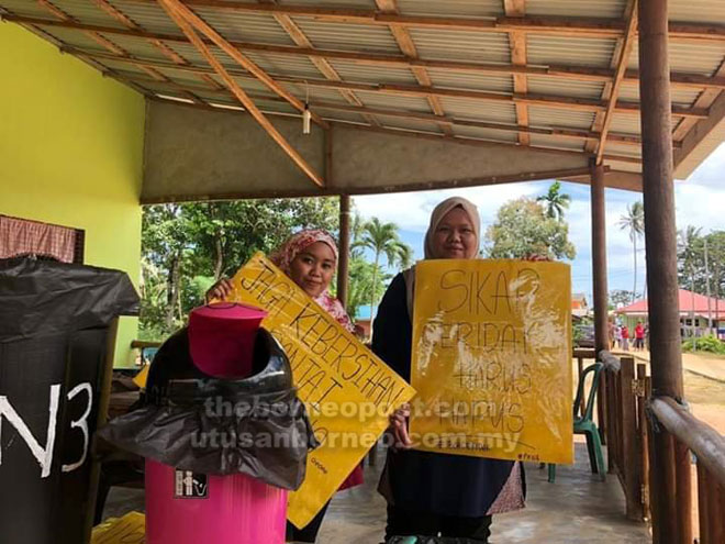 Petugas Pusat Khidmat DUN Tanjong Datu menunjukkan poster peringatan kepada pengunjung Telok Melano.