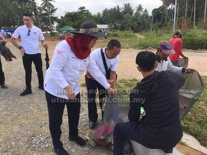 Jamilah (kiri) bersama penduduk Kampung Telok Melano gotong-royong mengutip sampah-sarap di kawasan pantai.