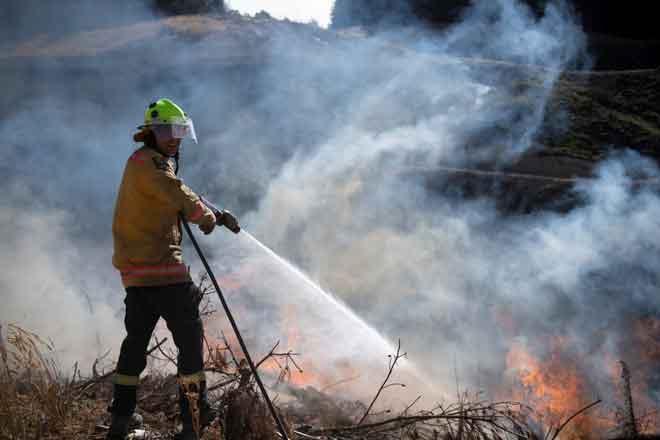 Anggota bomba pasukan pertahanan New Zealand memadamkan kebakaran Richmond dekat Nelson, South Island, New Zealand kelmarin. — Gambar Reuters