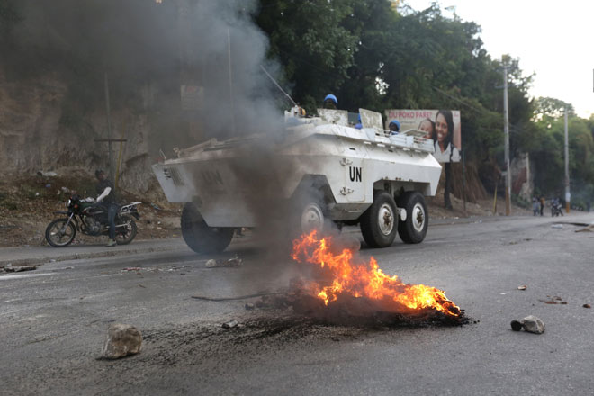 Sebuah kenderaan berperisai MINUJUSTH melintasi sekatan berapi semasa menangani protes antikerajaan di Port-au-Prince, kelmarin. — Gambar Reuters