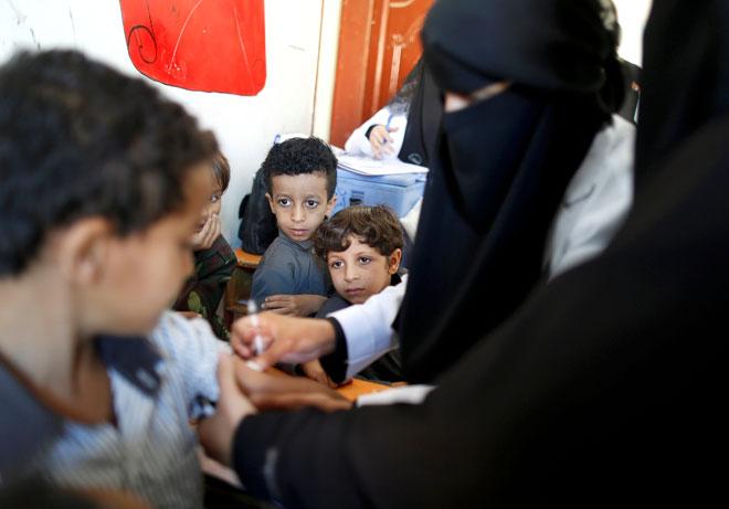 Para pelajar lain melihat seorang budak lelaki menerima vaksin demam campak dan rubella di sekolah mereka ketika program imunisasi enam hari dilancarkan di Sanaa, kelmarin. — Gambar Reuters