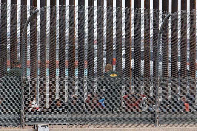 Migran dari Amerika Tengah dilihat diiringi pegawai Kastam dan Perlindungan Sempadan (CBP) selepas menyeberangi sempadan dari Mexico untuk menyerah diri kepada pegawai di El Paso, Texas, AS dalam gambar ini yang diambil dari Ciudad Juarez, Mexico pada Ahad. — Gambar Reuters