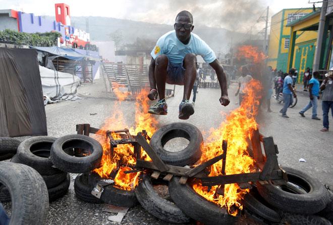 Seorang lelaki melompat di atas tayar yang terbakar semasa tunjuk perasaan terhadap kerajaan pimpinan Moise di jalan raya di Port-au-Prince, Haiti pada Ahad. — Gambar Reuters