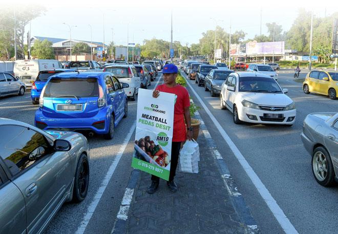 Pekerja 'Brehi Makang', Muhammad Zuhaili Rejab, 18, menjaja makanan bebola daging sos lada hitam di persimpangan lampu isyarat Jalan Tengku Mizan baru-baru ini. — Gambar Bernama