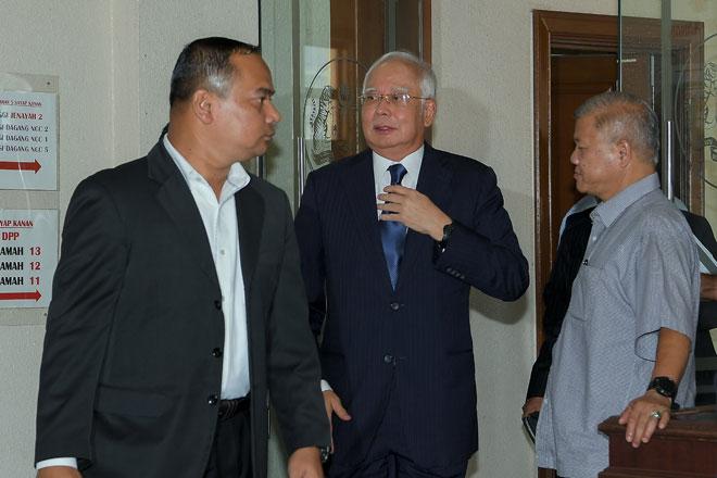 Najib (tengah) keluar dari Mahkamah Tinggi di Kuala Lumpur, semalam selepas mendengar sebutan kes tujuh pertuduhan yang dihadapinya berhubung dana SRC International Sdn Bhd berjumlah RM42 juta. — Gambar Bernama