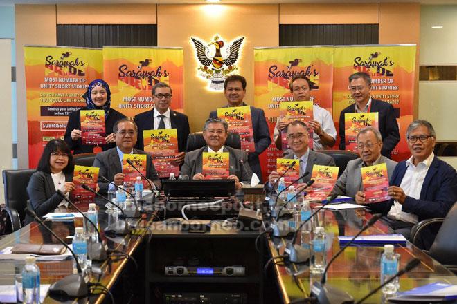 Morshidi (tengah) memegang ilustrasi iklan untuk 'Sarawak's Pride–Most Number of Unity Short Stories' bersama yang lain di Kuching, semalam.