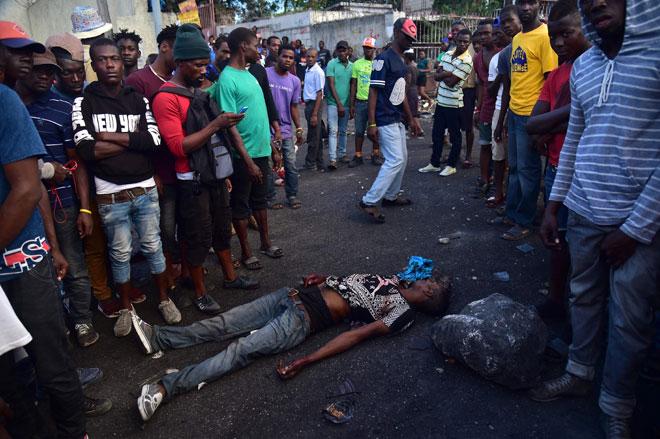 Orang ramai berdiri di sekeliling mayat seorang lelaki yang maut dalam pertelingkahan dengan polis sewaktu demonstrasi pada hari kelima protes di Port-au-Prince pada Isnin untuk membantah Presiden Haiti Jovenel Moise dan penyalahgunaan dana Petrocaribe. — Gambar AFP