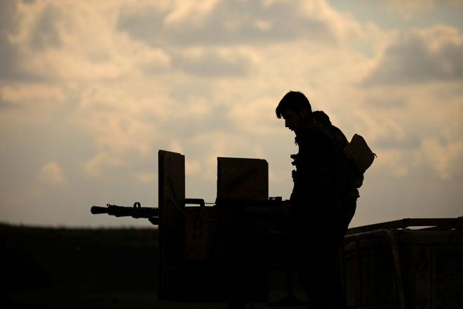Seorang anggota Tentera Demokratik Syria (SDF) berdiri di atas trak pikap yang dipasang dengan senjata dekat Baghouz, wilayah Deir Al Zor, Syria pada Isnin. — Gambar Reuters