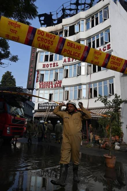 Kakitangan Jabatan Bomba Delhi                          (DFS) dan polis Delhi berdiri di luar Hotel Arpit Palace selepas memadamkan kebakaran yang berlaku di premis tersebut                               di New Delhi pada Selasa. — Gambar AFP