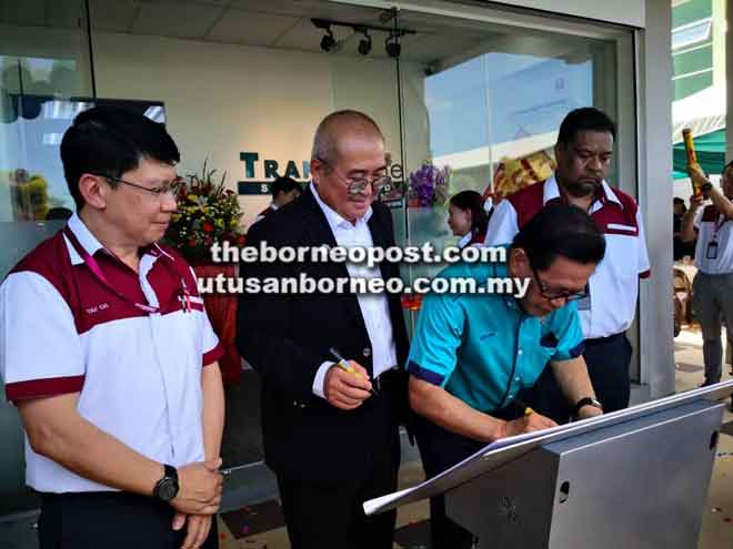 Lee menurunkan tandatangan beliau diikuti oleh Adam (dua kiri) sempena pembukaan rasmi pejabat Transfame di Miri semalam, sambil disaksikan oleh Tay (kiri) dan Kenneth.