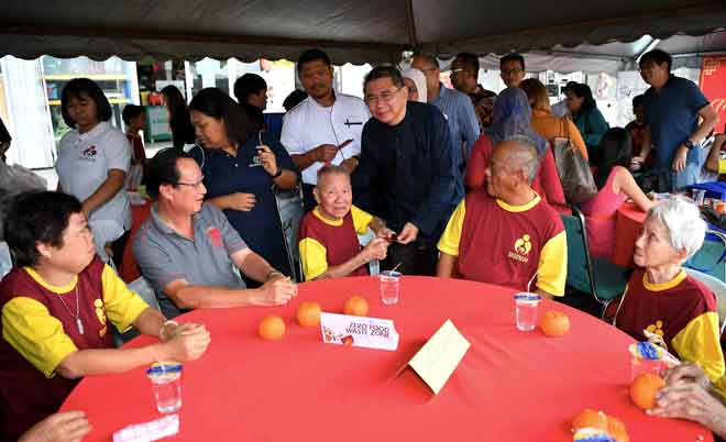 Salahuddin menyampaikan angpau kepada warga emas daripada Persatuan Kebajikan Amitabha Malaysia pada Program SWM Kasih Misi Sampul Merah @ Amitabha Malaysia di Jalan Tasek, Johor Bahru, semalam. —Gambar Bernama