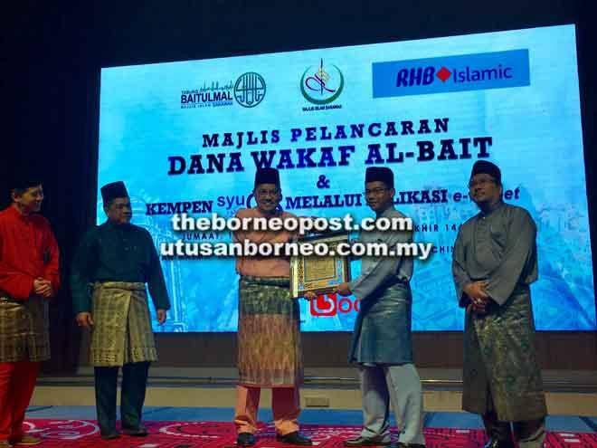 Abang Mohd Shibli menyampaikan cenderamata kepada Adissadikin pada majlis pelancaran Dana Wakaf Al-Bait dan Kempen syuQR melalui aplikasi e-Wallet Boost di Kuching, semalam.