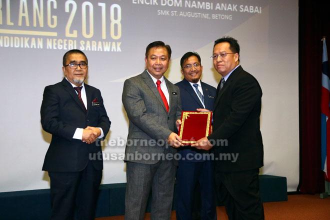 Dome Nambi Sabai (kanan) guru dari SMK St Augustine Betong menerima APC daripada Azhar.  — Gambar Muhammad Rais Sanusi