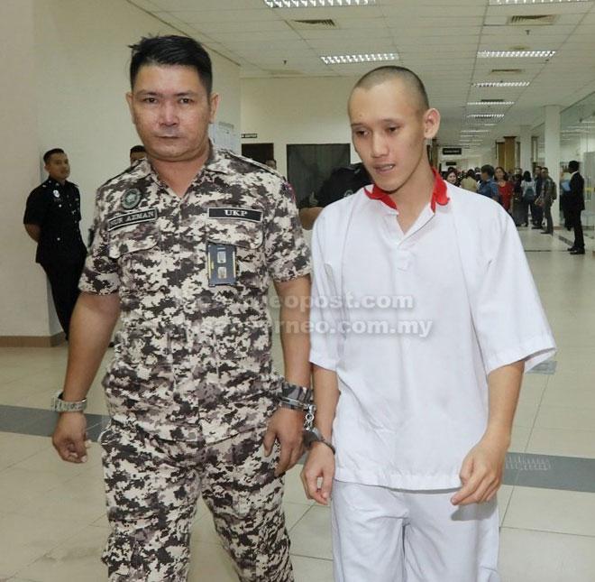 Alister diiringi pegawai penjara di Kompleks Mahkamah Negeri Sarawak semalam.