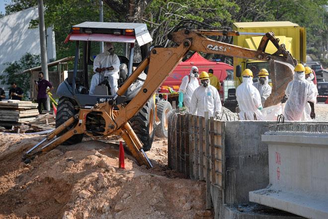 Kerja-kerja pembersihan dan pemeriksaan giat dilakukan di kawasan insiden pencemaran bahan kimia di Sungai Kim Kim dekat Pasir Gudang, Johor Bahru semalam. — Gambar Bernama