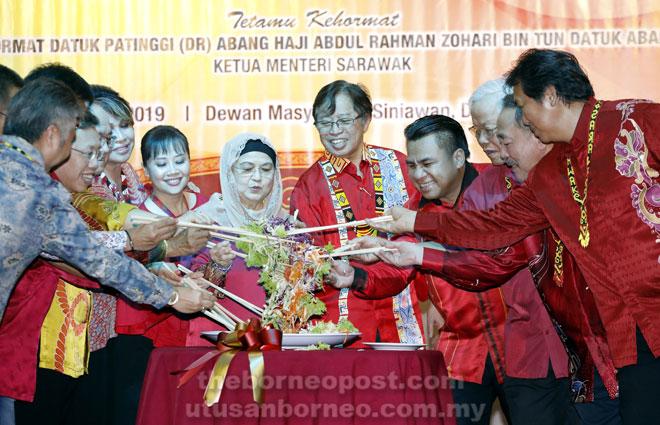 Abang Johari bersama isteri, Juma'ani (enam kanan), Miro (empat kanan) serta menteri kabinet dan wakil rakyat lain yang hadir melakukan simbolik upacara menggaul 'Yee Sang' sempena Majlis Makan Malam Tahun Baharu Cina 2019.
