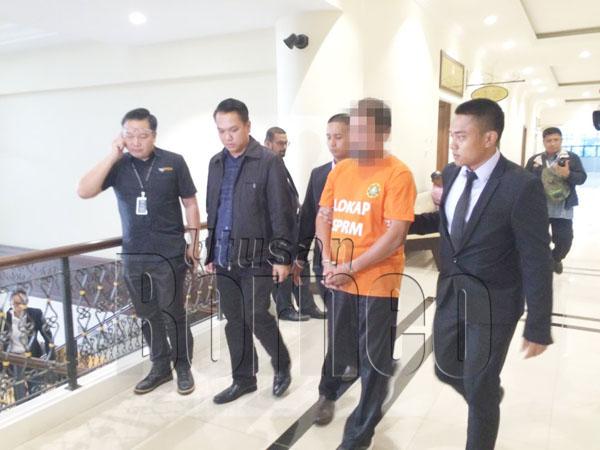 INDIVIDU terbabit (dua, kanan) diiringi pegawai SPRM keluar dari kamar Mahkamah Majistret.