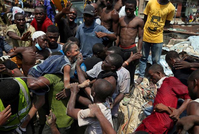 Orang ramai membantu mengangkat seorang budak di lokasi runtuhan sebuah bangunan yang menempatkan sebuah sekolah dan beberapa unit pangsapuri di ibu kota komersil Nigeria di Lagos pada Rabu. — Gambar Reuters