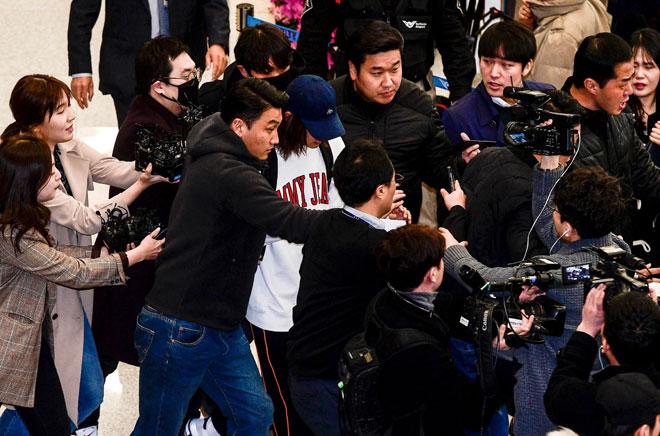 Gambar yang diambil pada 12 Mac ini menunjukkan Jung (bertopi) dikelilingi             pemberita ketika tiba di Lapangan Terbang Antarabangsa Incheon, Korea Selatan. — Gambar AFP