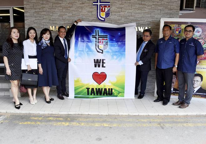 Pengurus Syarikat Top Green Tech Sdn Bhd (TGT) Albert J.Kok (empat kiri) menyerahkan banner kepada Alijus selepas pelancaran pemasangan Lightbox (Iklan elektronik) Majlis Perbandaran Tawau (MPT) semalam. — Gambar Bernama