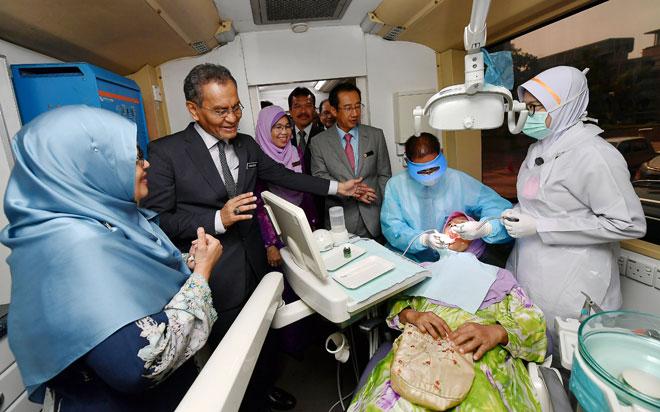 Dr Dzulkefly melihat proses mencuci gigi semasa melawat pameran sempena sambutan Hari Pergigian Kesihatan Sedunia 2019 di Kementerian Kesihatan, Putrajaya semalam. — Gambar Bernama