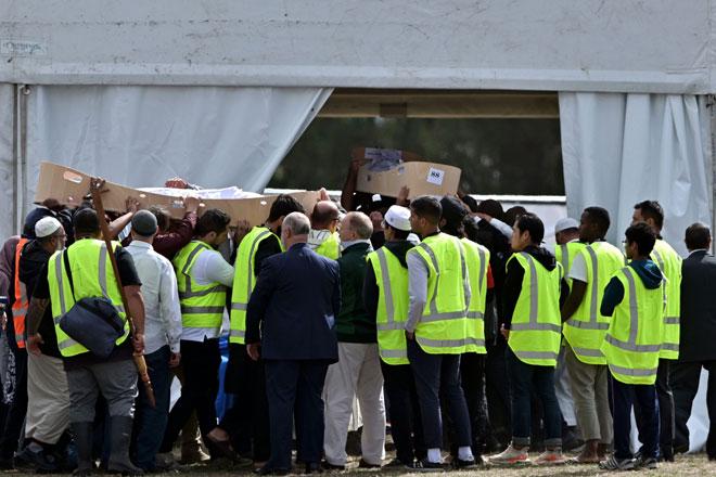 Orang ramai mengangkat keranda Khalid Mustafa dan anak lelakinya Hamza sewaktu pengebumian di tanah perkuburan Memorial Park di Christchurch, New Zealand pada Rabu. — Gambar AFP