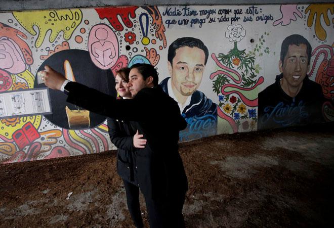 Saudara-mara Mercado dan Arredondo mengambil swafoto di hadapan mural yang                  menggambarkan dua pelajar tersebut di luar Universiti Tecnologico de Monterrey di Monterrey, Mexico pada Selasa. — Gambar Reuters