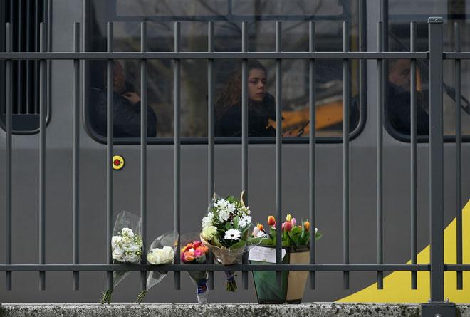 Seorang penumpang (tengah) dalam sebuah trem melihat bunga yang dipamerkan dekat lokasi serangan maut di 24 Oktoberplein di Utrecht, pada Selasa. — Gambar AFP