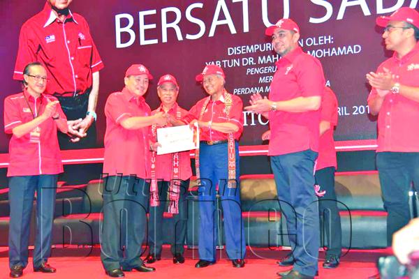 HAJIJI (dua, kiri) menyampaikan surat kebenaran penubuhan penaja bahagian kepada Tun Mahathir pada Majlis Pelancaran PPBM Sabah, pada Sabtu.