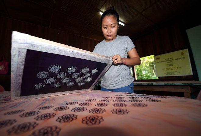 Lyona Stephen menggunakan teknik cetakan bagi mendapatkan latar belakang warna kain mengikut motif di Kampung Telian Tengah Mukah. — Gambar Bernama