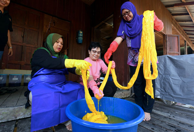 (Dari kiri) Saadiah Ibrahim, Pauling Jauhli dan Kartini Salihi membuat proses mewarna batik di Kampung Telian Tengah Mukah. — Gambar Bernama