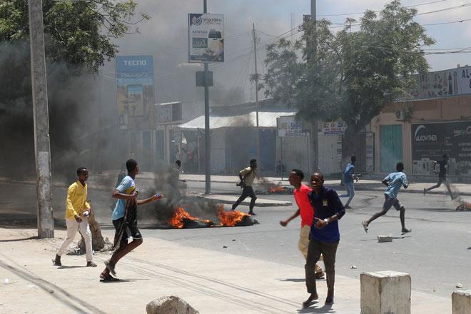 Para penunjuk perasaan berlari melintasi tayar-tayar yang dibakar semasa protes antipolis di Somali yang membunuh seorang pemandu teksi beca dan penumpangnya di Mogadishu, kelmarin. — Gambar Reuters