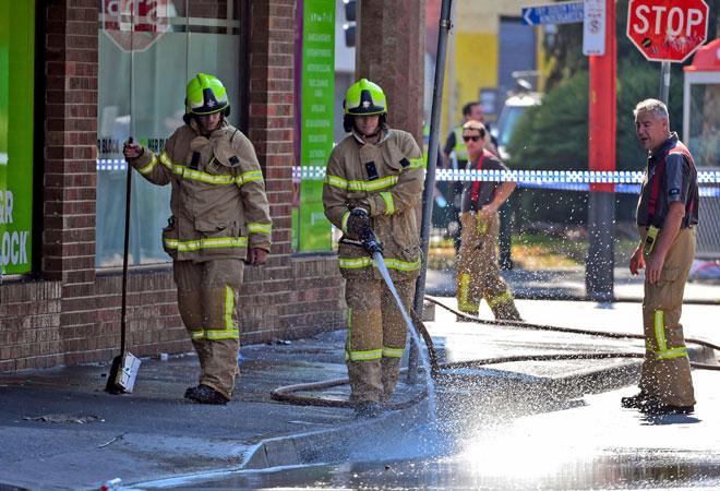 Anggota bomba membersihkan tumpahan darah selepas seorang pengawal keselamatan ditembak mati di luar sebuah kelab malam yang popular di Melbourne, semalam. — Gambar AFP
