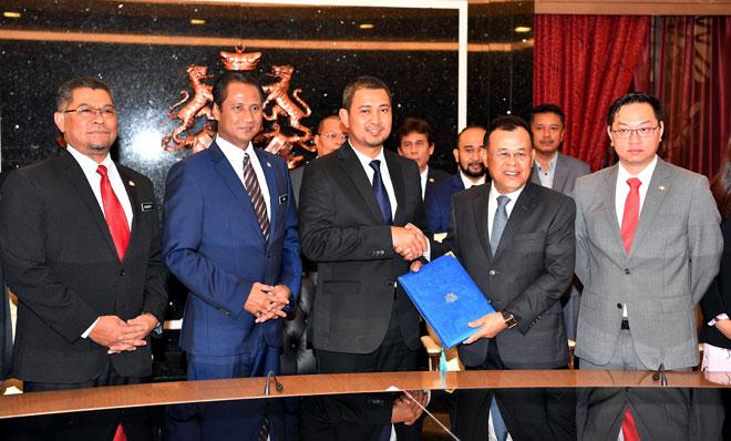Dr Sahruddin (tengah) menerima nota serah terima tugas daripada Osman (dua kanan) pada Majlis Serah Terima Tugas di Bangunan Dato Jaafar Muhammad, Kota Iskandar, Iskandar Puteri semalam. — Gambar Bernama