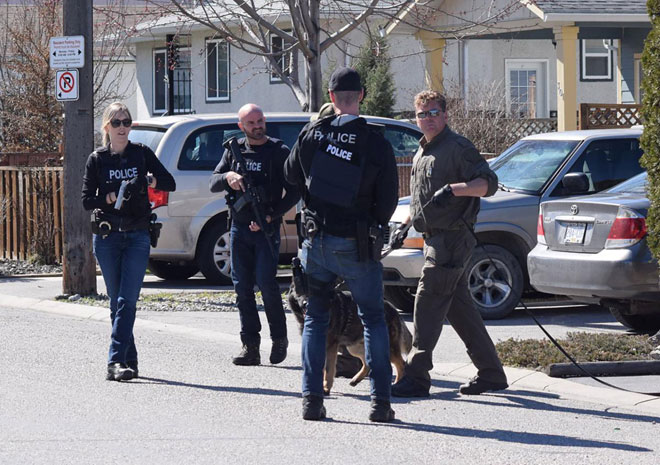 Pegawai polis bersenjata mencari seorang suspek di Haynes Street, sewaktu siri serangan di mana empat orang ditembak mati, di Penticton, British Columbia pada Isnin. — Gambar Reuters