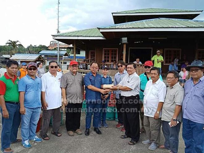 Kennedy (lima kiri) menyampaikan sumbangan kepada wakil  penduduk Uma Bawang.