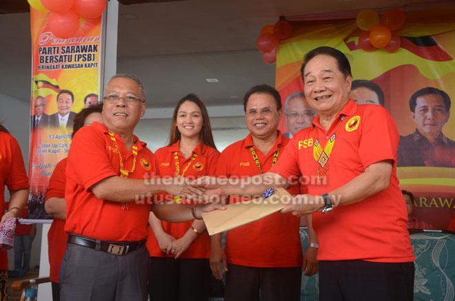 Wong (kanan) menerima borang permohonan menyertai PSB daripada Pengerusi Pengelola PSB Kapit Datuk Kristoffer Nyuak sambil diperhatikan Entulu (dua kanan).