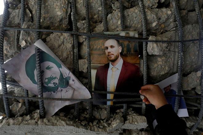 Seorang lelaki menggantung gambar Barghouti pada puing rumah Barghouti yang sebahagiannya dimusnahkan oleh tentera Israel di perkampungan Kobar berhampiran Ramallah, dalam wilayah Tebing Barat yang diduduki Israel pada Rabu. — Gambar Reuters