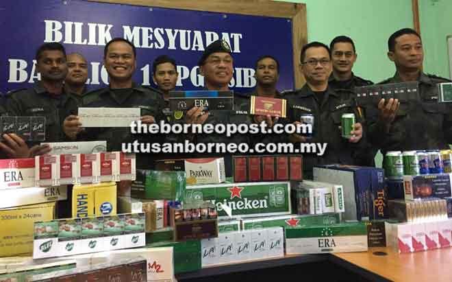 Sanudin (tengah) menunjukkan rokok dan bir seludup yang dirampas pada sidang akhbar semalam.