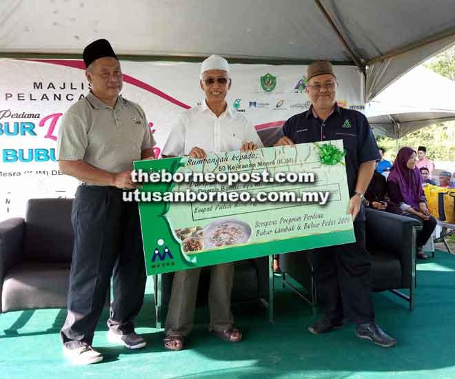 Abang Wahap (tengah) menyampaikan replika cek bernilai RM40,700 kepada wakil 50 KJM DBKU.