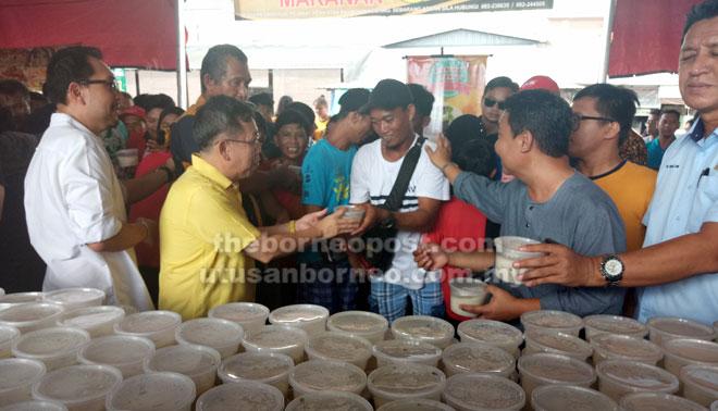 Dr Sim mengagihkan bubur lambuk kepada pengunjung di Bazar Ramadan Stutong di Kuching semalam. Turut kelihatan pengerusi penganjur Azizi Morni (kiri).