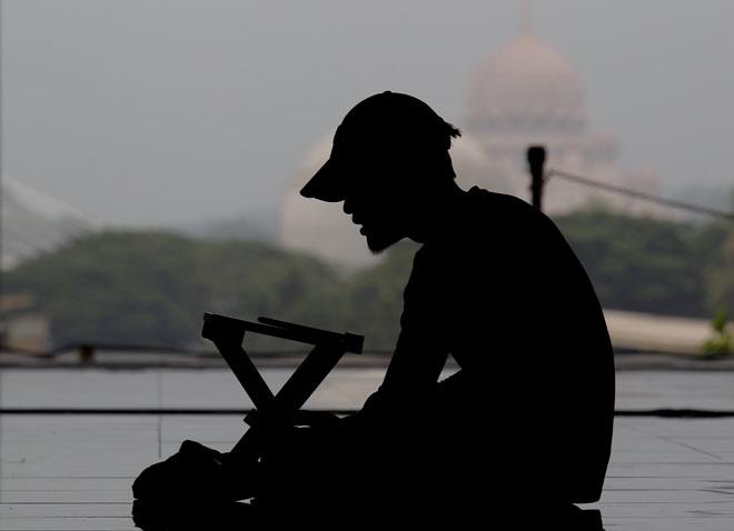Rakaman gambar 'silhouette' seorang lelaki membaca ayat-ayat suci al-Quran ketika tinjauan sempena Ramadan di Masjid Tuanku Mizan Zainal Abdidin, Putrajaya, semalam. — Gambar Bernama