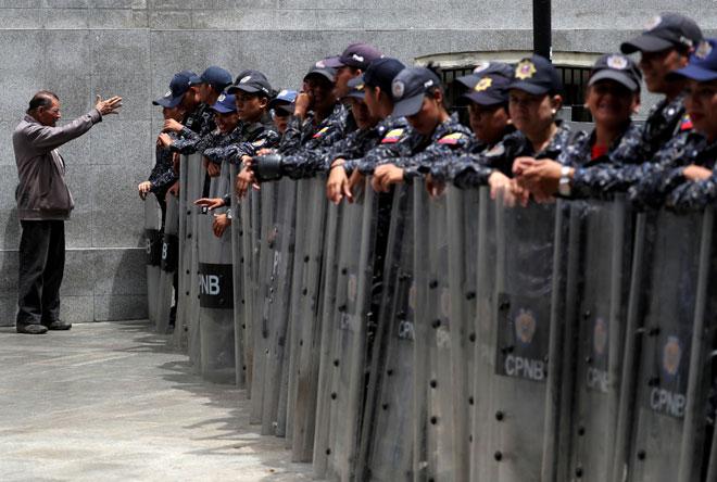 Anggota Pasukan Pengawal Negara Venezuela berdiri dalam barisan di luar bangunan               Dewan Negara di Caracas kelmarin. — Gambar Reuters