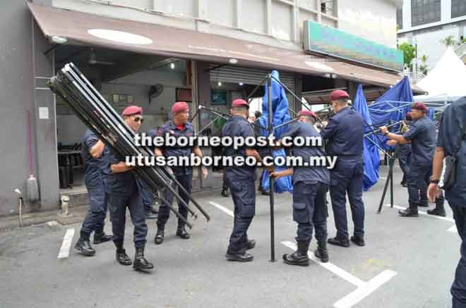 Kelihatan anggota penguat kuasa DBKU membuka kanopi di hadapan sebuah kedai di Satok.